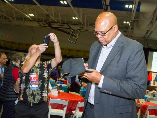 "Rick Michaels, left, takes a photo while Pistons ""Bad Boy"" James Edwards signs his hat at the 2017 Night of Champions benefit for the YMCA of the Blue Water Area Oct. 26."