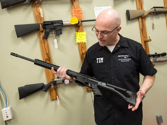 The Hock Shop and Sporting Center owner Tim Daniels holds a 450 Bushmaster rifle inside his shop in Port Huron Feb. 28. The rifle looks like an AR-15 rifle, but it shoots a straight-walled pistol cartridge and is legal in zone three hunting areas.