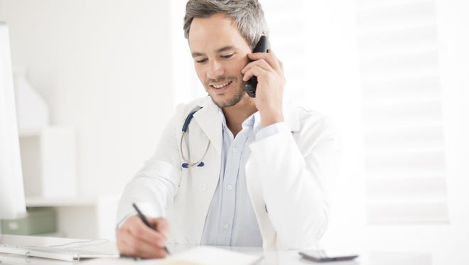 young doctor on phone at his office