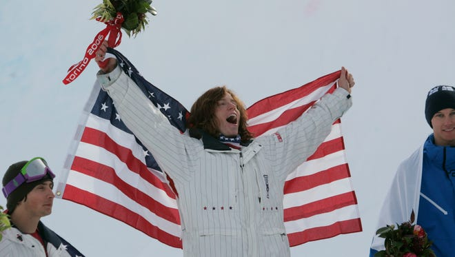 Shaun White celebrates on the podium after winning gold in the men's halfpipe in 2006.
