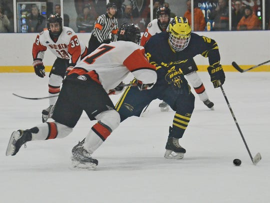 Hartland's Alex Krause skates with the puck while defended