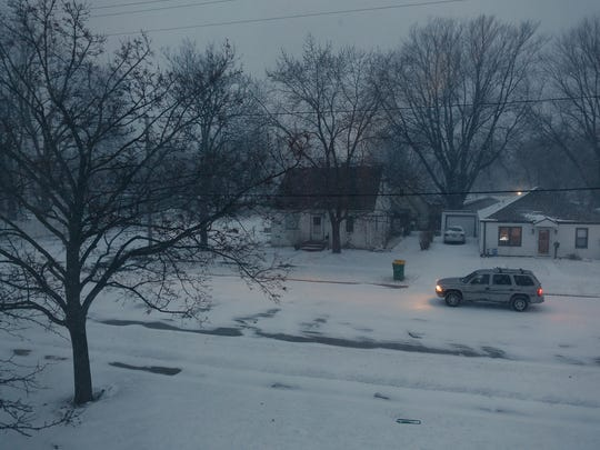 A car navigates a snowy residential street Monday in Green Bay.