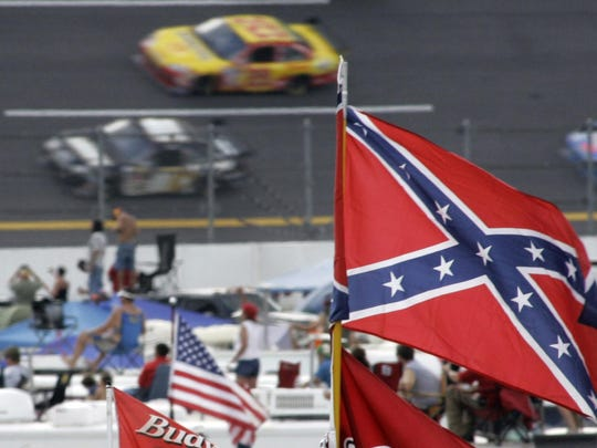 In this Oct. 7, 2007, file photo, a Confederate flags fly in the infield as cars come out of turn one during a NASCAR auto race at Talladega Superspeedway in Talladega, Ala.