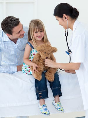 Female doctor and happy little girl examing a teddy bear