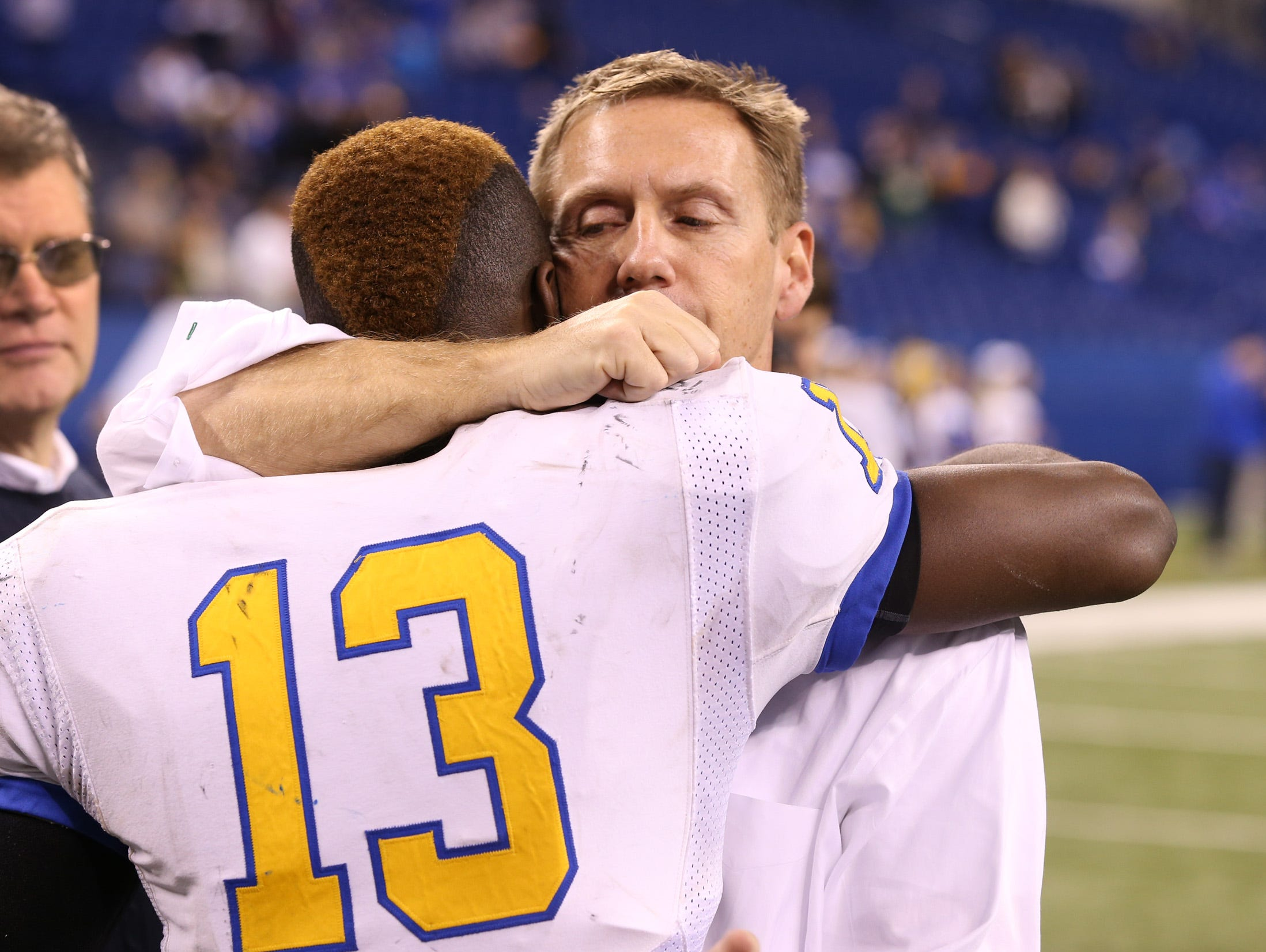 Carmel's head coach Kevin Wright hugs his quarterback Isaac James after their 6-7 loss to Warren Central. The Carmel Greyhounds play the Warren Central Warriors in the IHSAA Class 6A football championship game Saturday, November 30, 2013, evening at Lucas Oil Stadium. Matt Kryger / The Star