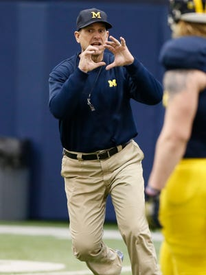 Michigan football coach Jim Harbaugh demonstrates what he wants from running backs catching passes during practice Thursday, March 19, 2015, in Ann Arbor.