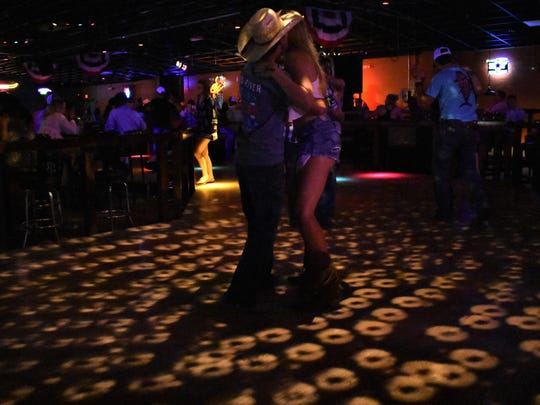A couple dances while a country music band plays in the background on June 23, 2018 at Midnight Rodeo in San Angelo. The club was known for its live concerts and dance floor.