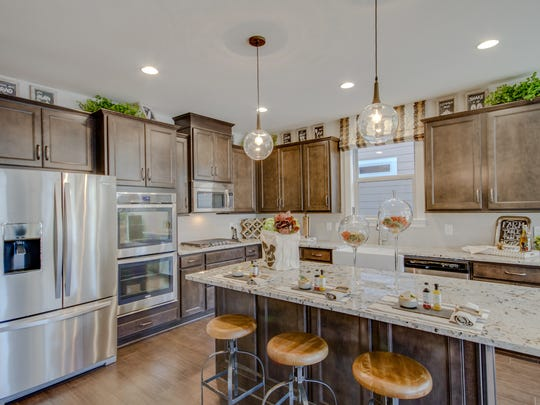 Many new homes, like this one by Drees in Durham Farms, are being built open kitchens that feature islands with seating. It's the new hub for guests and family alike.