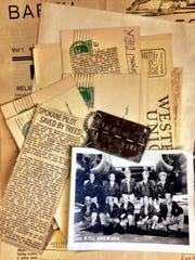 Loren Rice's mementos of his time as a German-held prisoner of war include newspaper clippings, telegraphs, a photo of his bombing crew and POW tag.