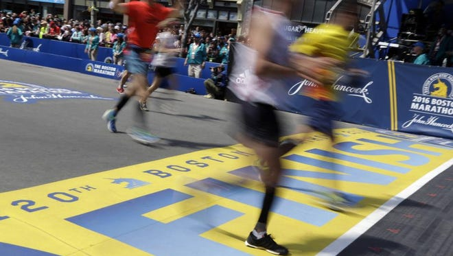 Runners cross the finish line of the 120th Boston Marathon on Monday, April 18, 2016, in Boston.