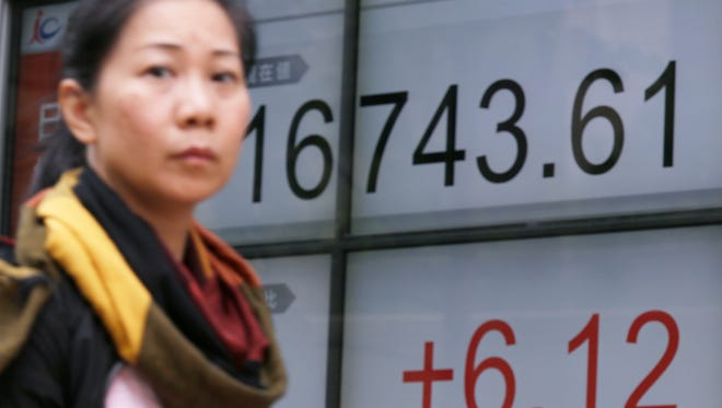 A woman walks past an electronic stock board showing Japan's Nikkei 225 index at a securities firm in Tokyo, Tuesday, Aug. 30, 2016.