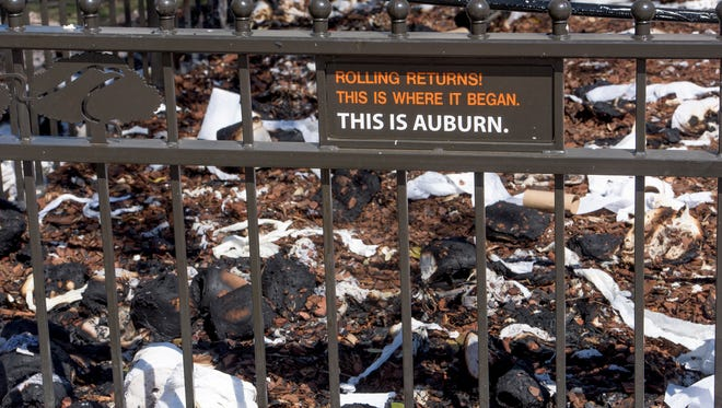 Burned toilet paper litters the ground below the oak tree at Toomer's Corner in Auburn, Ala., that was left a bit charred on Sunday morning September 25, 2016 after being set on fire Saturday night after being rolled following Auburn's win over LSU.