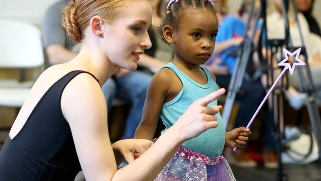 Lei'Lani Harmon, 3, holds onto the hand of Addison Spey, with the Cary Ballet Company, on April 20, 2017 during Plie All Day, an outreach program that hopes to bring dance to women's shelters throughout the Triangle.