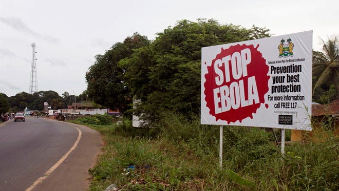 A billboard reading 'Stop Ebola' on the Masiaka Highway, forming part of a trans-West African highway, which links all West African States, on the outskirts of  the capital city of Conakry, Guinea.