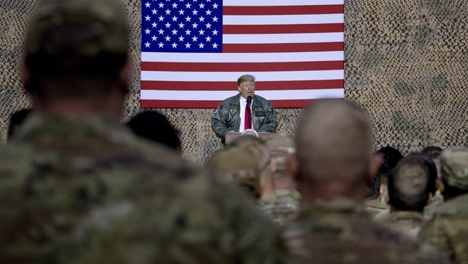 President Donald Trump is shown in December 2018 speaking to members of the military at a hangar rally at Al Asad Air Base, Iraq.