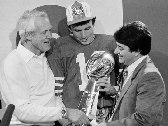 In this Jan. 20, 1985, file photo, San Francisco 49ers owner Edward DeBartolo Jr., right, congratulates coach Bill Walsh, left, and quarterback Joe Montana in the locker room at Stanford Stadium following their Super Bowl XIX win over the Miami Dolphins in Stanford, Calif. The Super Bowl returns to the technology-rich, football-crazed Bay Area for the first time since 1985 to celebrate its 50th edition.