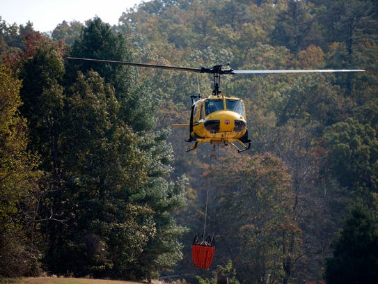 A helicopter carrying 240 gallons of water takes off