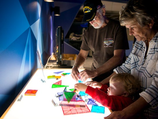 Twenty-two-month-old Milo Galloway plays with an interactive