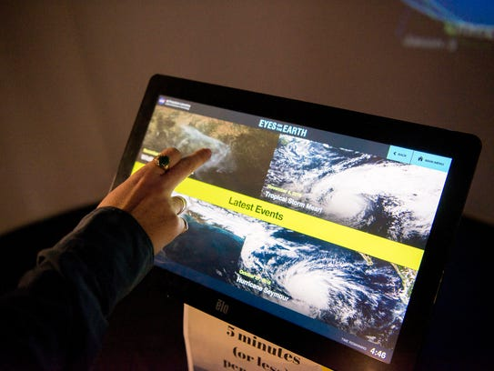 A visitor interacts with a display that tracts satellites,