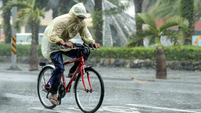 A man braves heavy rains as Typhoon Megi hits  Taiwan on Sept. 27, 2016. Typhoon Megi hit Taiwan with heavy winds, causing coastal high waves and flooding rains, according to media reports.