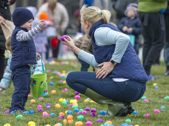 Audra Blasdel helps her son, Landon Blasdel, 2, of Speedway, hunt for eggs at the Indianapolis Motor Speedway on March 31, 2018.