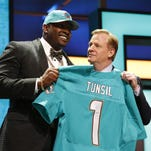 Offensive tackle Laremy Tunsil, left, from Ole Miss shows off his new Miami Dolphins jersey with NFL Commissioner Roger Goodell on Thursday. The Dolphins selected Tunsil with the 13th pick of the first round of the NFL Draft.