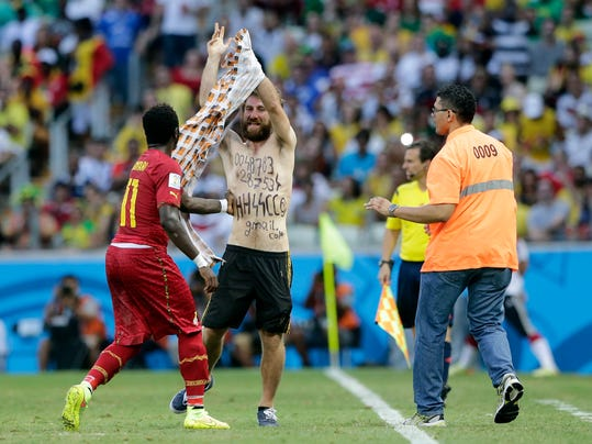 Ghana's Sulley Muntari helps to assist a man from the pitch after he ran on during the group G World Cup soccer match between Germany and Ghana at the Arena Castelao in Fortaleza, Brazil, Saturday, June 21, 2014. (AP Photo/Matthias Schrader)