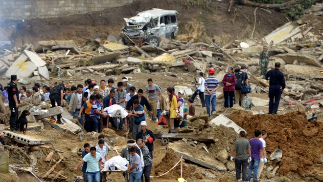 In this Thursday Aug. 28, 2014,photo, residents remove bodies in the aftermath of a landslide at Yingping village in Fuquan city in southwest China's Guizhou province.