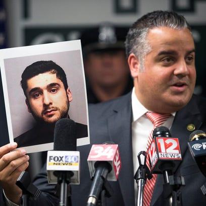Binghamton Mayor Richard David holds a photograph of