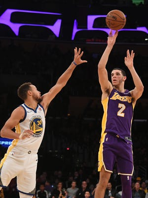 Lonzo Ball shoots over Stephen Curry.