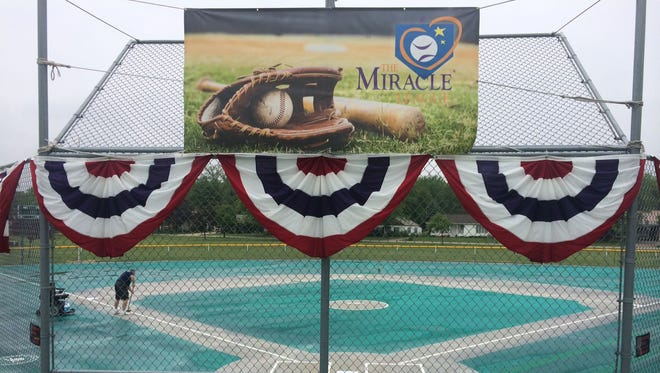 Red, white and blue bunting hangs atop the backstop fence at Resch Miracle Field in Allouez Optimist Park as Miracle League of Green Bay executive director Paul Liegeois sweeps away standing water on the field Friday afternoon, May 27, 2016. The 11th baseball season of the Miracle League for children 4 to 19 with disabilities starts Saturday, June 4.