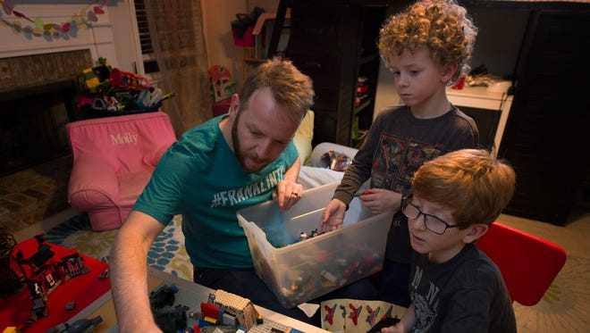 Josh Collins enjoys playing with Legos with his sons Jonas 7, and Riley 10, in their playroom at their home Friday Jan. 13, 2017, in Spring Hill, Tenn.