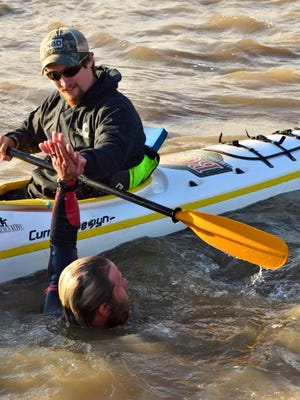Navy veteran Chris Ring, in the water, high fives Seth Mortenson as he crosses mile marker 0 in his swim down the Mississippi River. Mortenson spent six days a week over the last six months in the escort kayak ensuring Ring's safety as he guided him down the river.
