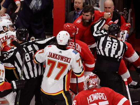Linesman Scott Driscoll (68) keeps Detroit Red Wings right wing Luke Witkowski (28) away from the Calgary Flames during the third period of an NHL hockey game, Wednesday, Nov. 15, 2017, in Detroit. (AP Photo/Carlos Osorio)