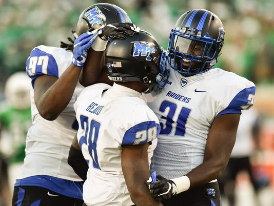 Middle Tennessee senior cornerback Dontavious Heard (28) celebrates with his teammates after he made a sack against the North Texas offense at Apogee Stadium