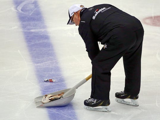 "An ice worker removes a fish during the second period of Game 1 of the NHL hockey Stanley Cup Finals between the Pittsburgh Penguins and Nashville Predators on Monday, May 29, 2017, at PPG Paints Arena in Pittsburgh. Authorities said Jacob Waddell, of Nolensville, Tenn., is facing charges after allegedly throwing a dead catfish onto the ice during the hockey game, including misdemeanor counts of possessing instruments of crime and disrupting meetings or processions, as well as a summary count of disorderly conduct. The Tennessee Bureau of Investigation commented on social media that investigators had never seen an ""instrument of crime"" like that. (AP Photo/Gene J. Puskar)"