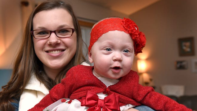 Danielle Lefebvre and her daughter Charleigh Mae on Monday, Dec. 21 at their home in Clearwater. Charleigh Mae spent time in the NICU at the St. Cloud Hospital and Lefebvre is giving back with a percentage of her Charleighs Halos headband sales.