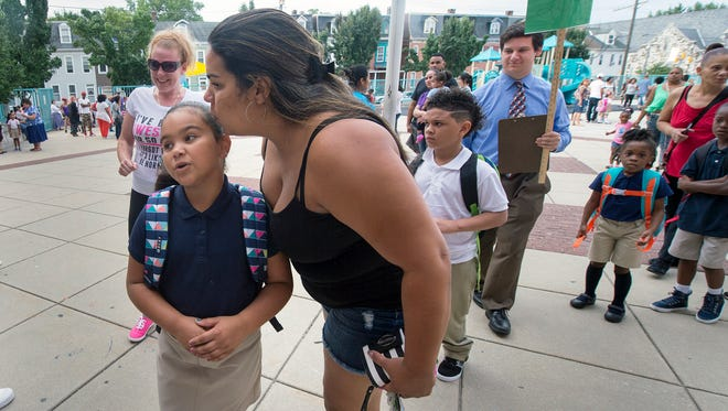 Suesly Marin, right, gives her daughter Shayned Hernandez a kiss as the line for her class enters Lincoln Charter School in York for the first day of school. Many students and parents said they like having the school year start early.