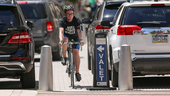 A bicyclist weaves in between cars in the valet parking area of the Conrad Hotel, downtown Indianapolis, Wednesday, June 21, 2017. The Cultural Trail passes through the valet area, posing a threat to pedestrian and cyclists.