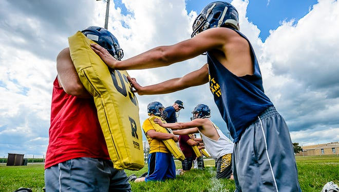 Pewamo-Westphalia Head Football Coach Jeremy Miller ,center, watches his defensive linemen in a quickness drill during the first practice of the new football season Monday August 7, 2017 in Westphalia.  KEVIN W. FOWLER PHOTO