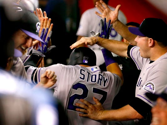 Colorado Rockies shortstop Trevor Story (27) is greeted in the dugout after hitting his first career home run during the third inning of a baseball game against the Arizona Diamondbacks, Monday, April 4, 2016, in Phoenix. (AP Photo/Matt York)