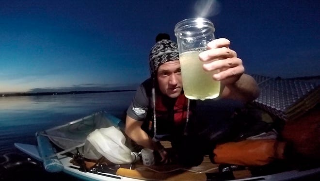 Christian Shaw of Ithaca, with the Plastic Tides group looks at their first sample from Cayuga Lake during their November sampling expedition that found plastic microbeads in Cayuga Lake.