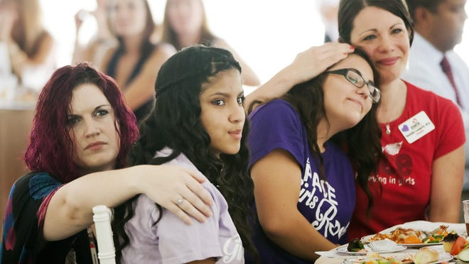 PACE Center for Girls, Lee County counselors Danielle Langevin, left, and Kendra Pugh, right, comfort two girls as they listen to the girls' video testimonial during PACE's annual luncheon at the center in Fort Myers.