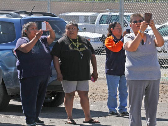 Community members watch as law enforcement officials escort Tom Begaye  from the Farmington Municipal Court building on Wednesday. Begaye faces charges of kidnapping and murder in connection to the abduction and death of 11-year-old Ashlynne Mike.