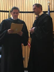 Jonathan H. Rosenbluth, at right, takes his oath to