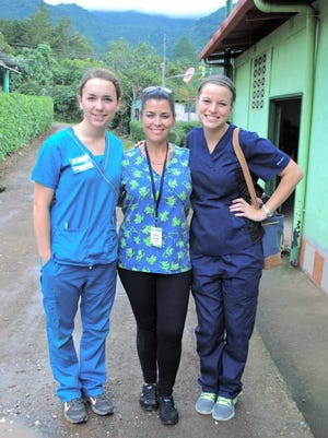 In this June, 2014 photo, U.S. citizen Sondra Lynn, center, poses with two unidentified fellow volunteers in Costa Rica. Lynn who organized volunteer medical missions in Central America was found stabbed to death on Thursday, Dec. 10, 2015, in the capital of Costa Rica. Police say the body was found on a bed at a San Jose hotel. (Vida Volunteer Travel via AP)