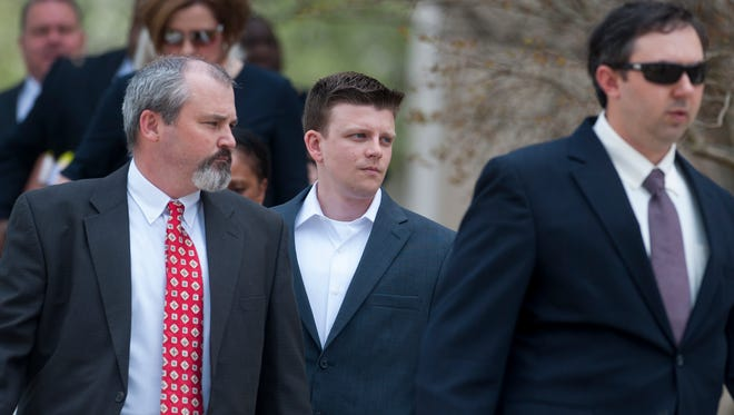 A.C. Smith, center, arrives for a hearing at the county courthouse in Montgomery, Ala. on Thursday March 24, 2016.  Montgomery Police Officer A.C. Smith has been charged with murder in the shooting death of Greg Gunn.