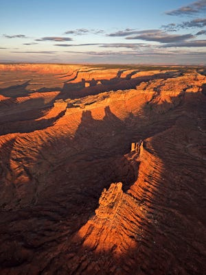 An aerial view of the southeastern edge of Cedar Mesa is pictured just after sunrise. To the west and southwest, unnamed monuments in Valley of the Gods cast long shadows in the morning light. Navajo Mountain is on the left horizon.