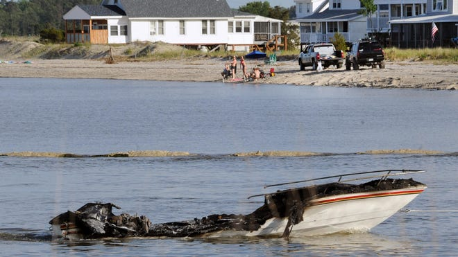 Bowers Volunteer Fire Company officials tow what's left of a small boat that caught fire Sunday about a quarter-mile off of Bowers Beach.