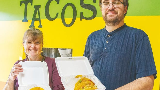 Patti Wieskamp, left, and Corey Schuhmacher, right, hold up freshly-made tacos inside their restaurant, PC Tacos.